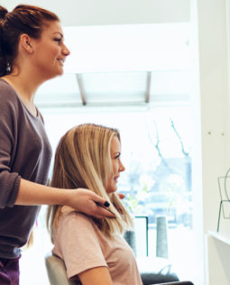smiling-hairdresser-finishing-a-female-clients-SKUZCFX