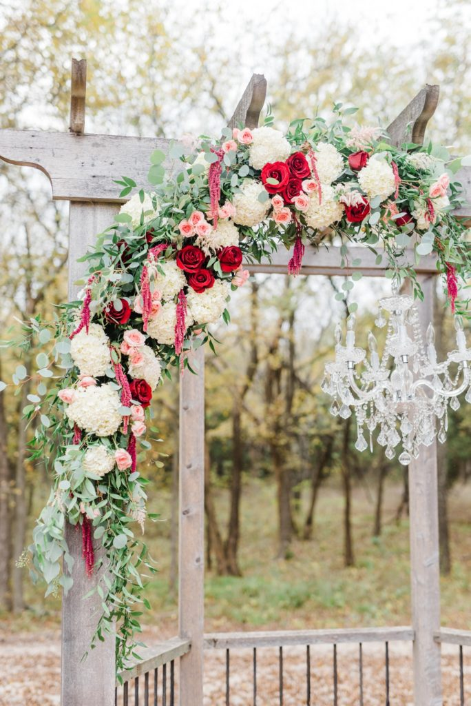 Red and pink floral wedding arch