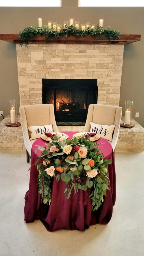 sweetheart table with greenery by fireplace for winter wedding