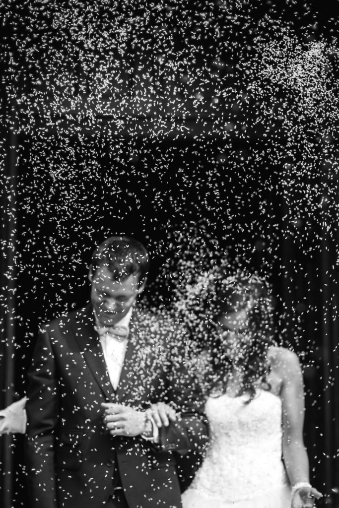 bride and groom exiting wedding with confetti