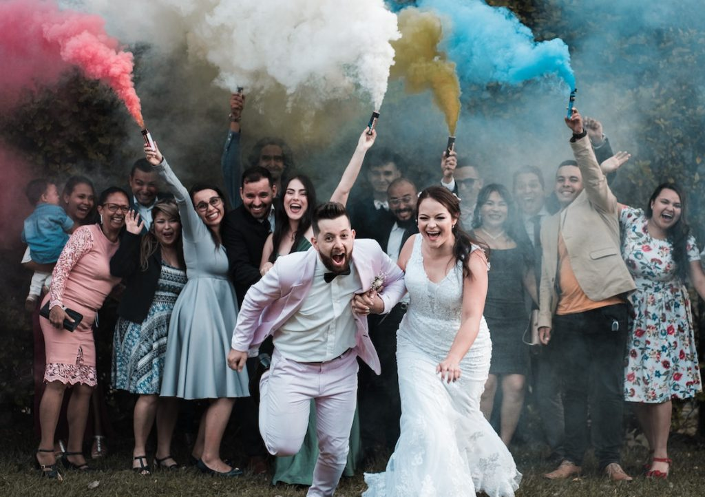 bride and groom and guests with smoke bomb at wedding reception