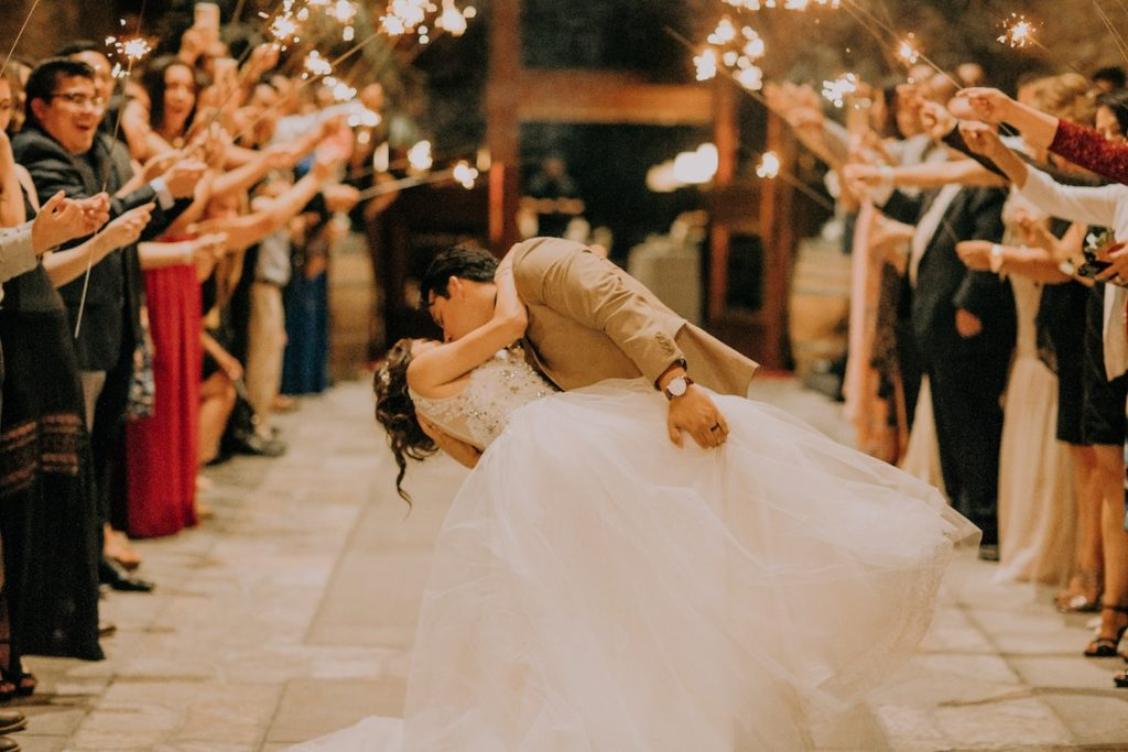 bride and groom exiting reception while guests hold sparklers