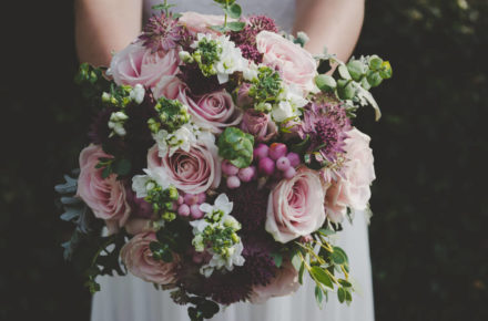 A bride holding flowers in front of herself.